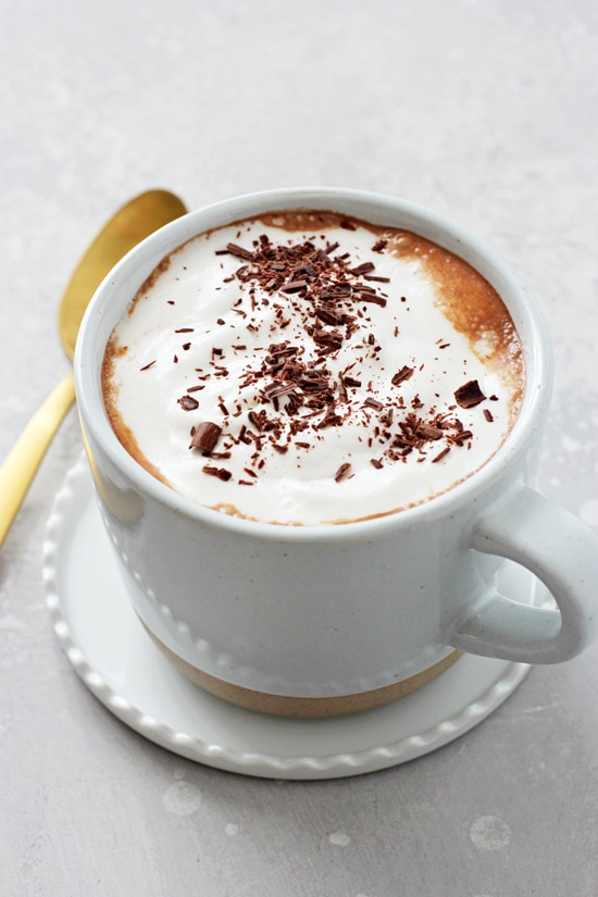 A white mug on a saucer filled with Dairy Free Hot Chocolate.