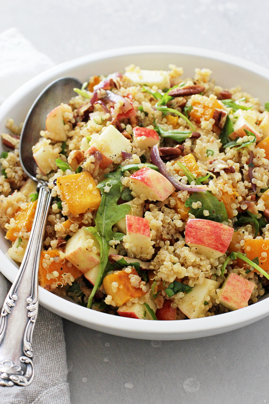 A white bowl filled with Harvest Quinoa Salad with a serving spoon.