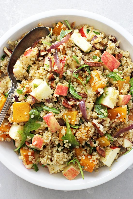 A white dish filled with Apple Quinoa Salad and a serving spoon.