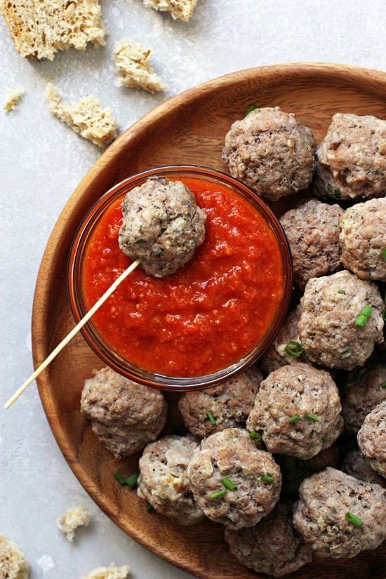 Eggless Meatballs on a wooden plate with a small bowl of marinara sauce.
