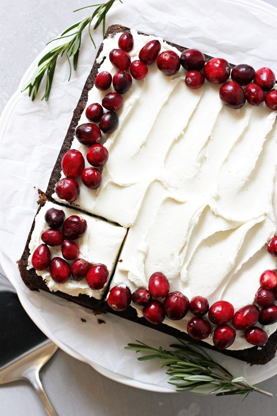 A Vegan Gingerbread Cake on a cake stand topped with fresh cranberries.