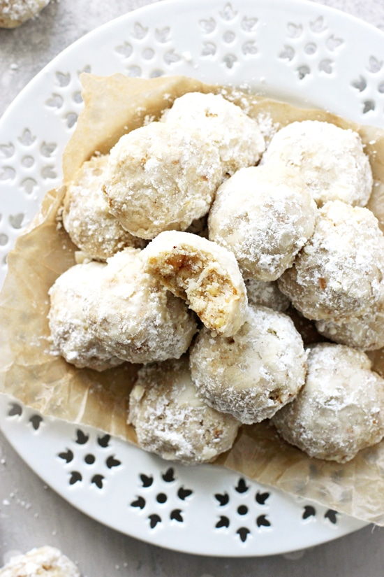 A plate of Vegan Mexican Wedding Cookies with a bite taken out of one.