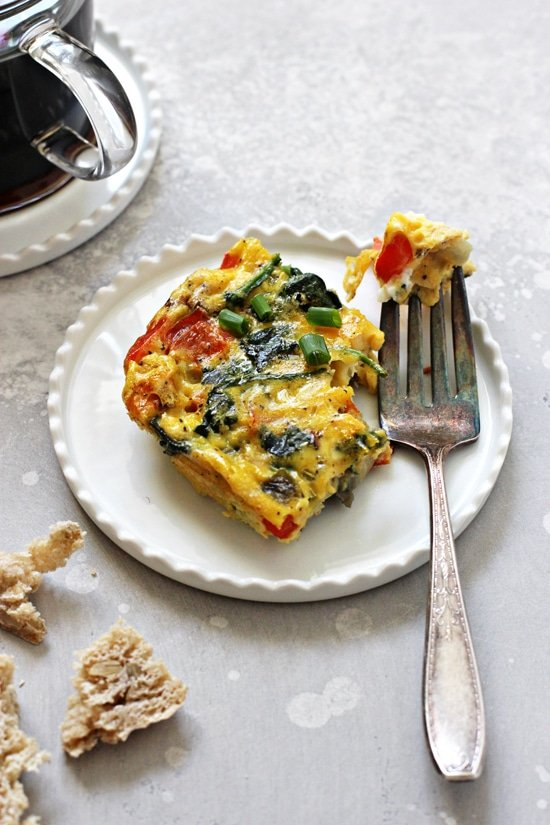 A slice of Dairy Free Egg Frittata on a plate with a bite taken out with a fork.