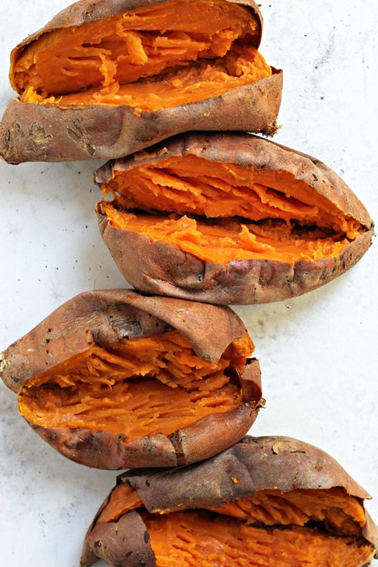 Four baked sweet potatoes on a white surface.
