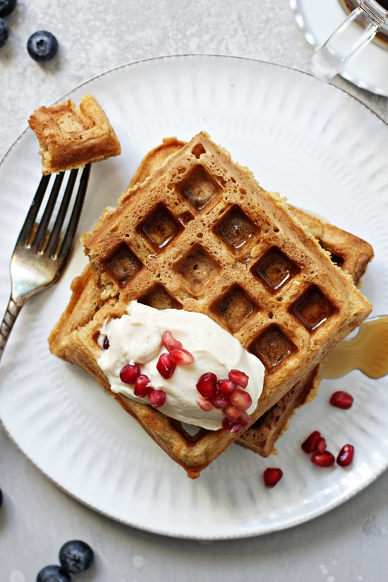 Two Dairy Free Waffles on a plate with a bite taken out with a fork.