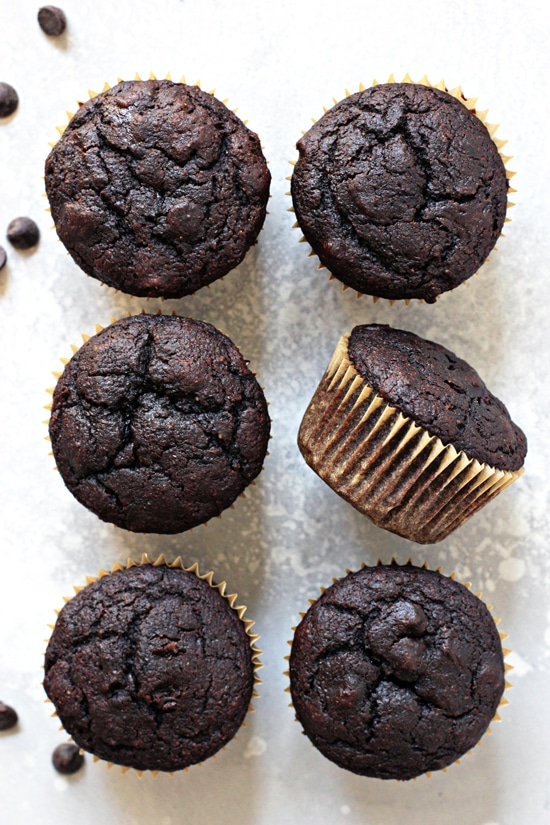 Six Dairy Free Double Chocolate Muffins on a grey surface.