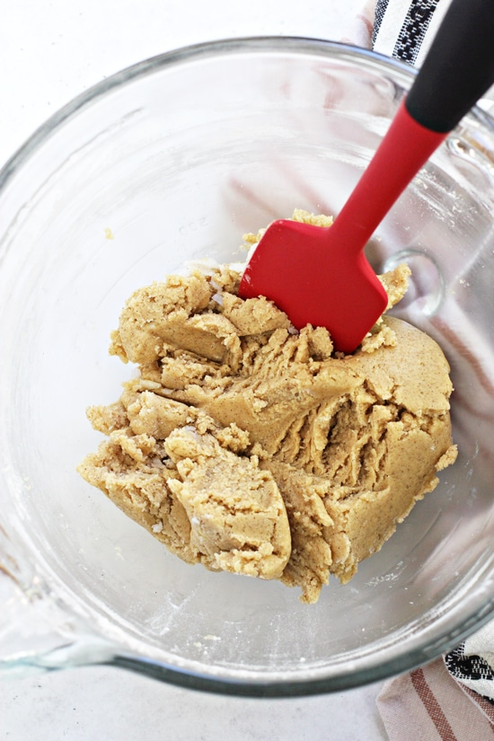 A glass mixing bowl filled with cookie dough and a spatula.