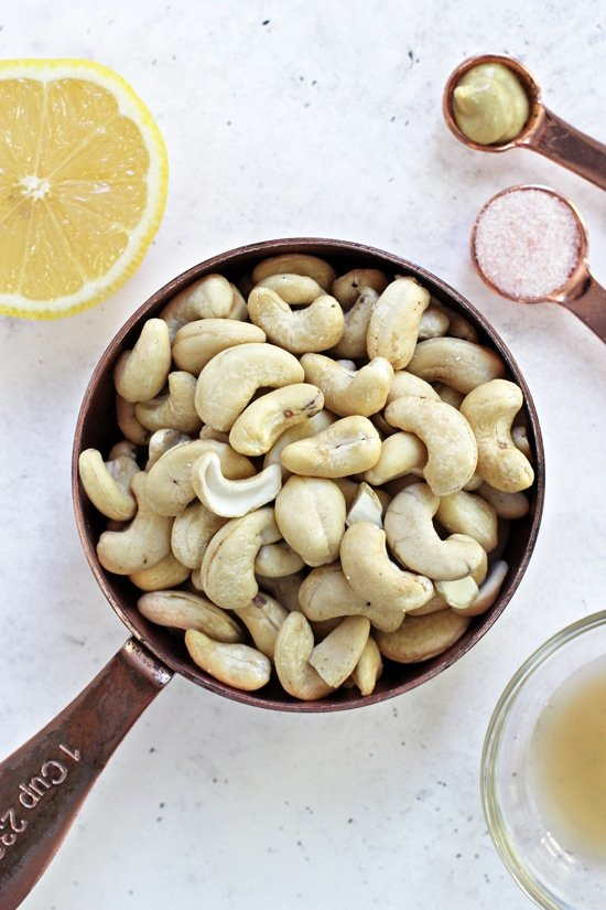 Raw cashews, lemon juice, mustard and salt in measuring cups and spoons.