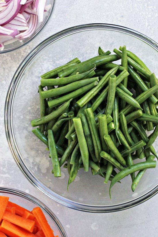 Fresh green beans, carrots and sliced red onion in glass bowls.