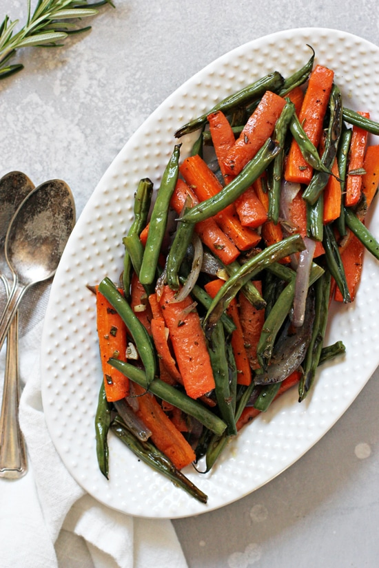 Roasted Green Beans and Carrots on a serving platter with spoons to the side.