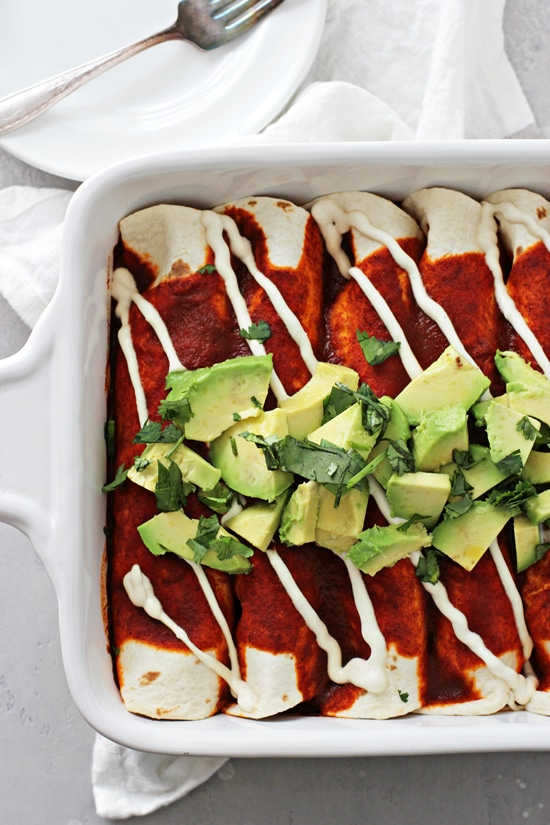 A baking dish with No Cheese Enchiladas and plates to the side.