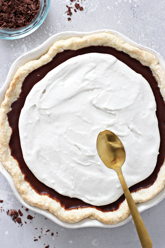 A pie with whipped topping being spread on with a spoon.