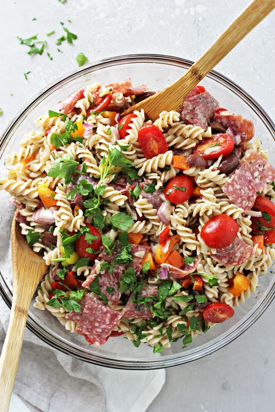 A glass mixing bowl filled with Dairy Free Italian Pasta Salad.