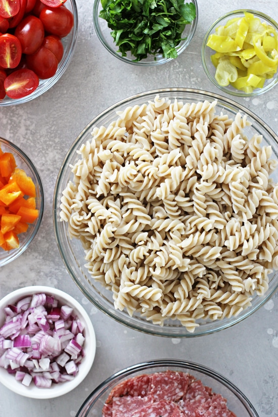 Cooked pasta and chopped veggies in glass bowls.