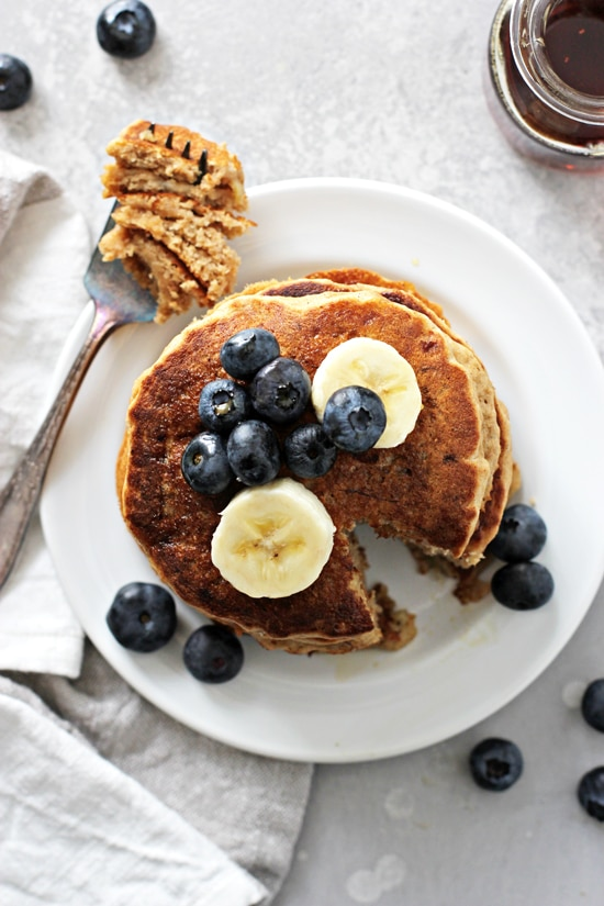 A stack of Healthy Banana Pancakes with a bite taken out with a fork.