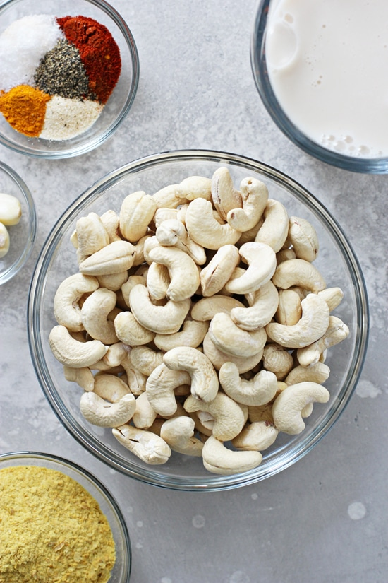 Cashews, spices and almond milk in bowls.