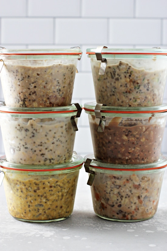 Six jars of oatmeal stacked on a grey surface.