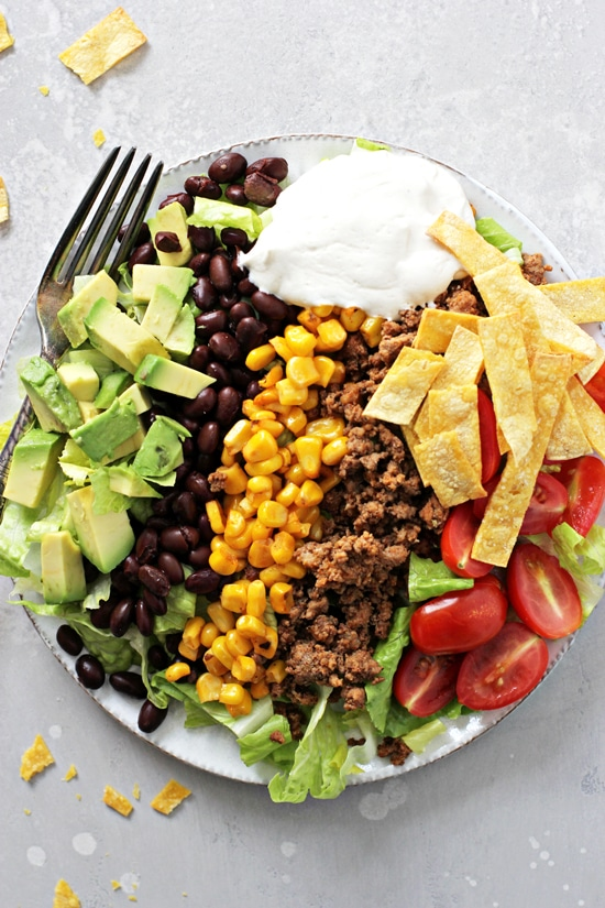 Gluten Free Taco Salad on a white plate with a fork.