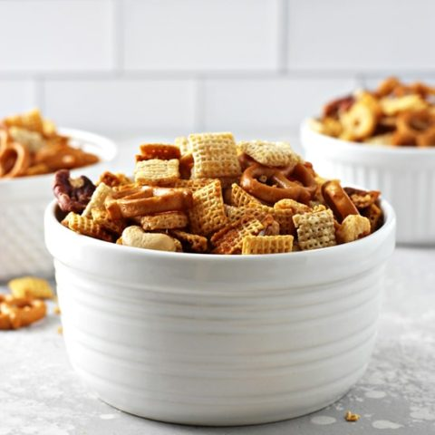 Three white bowls filled with Dairy Free Chex Mix.
