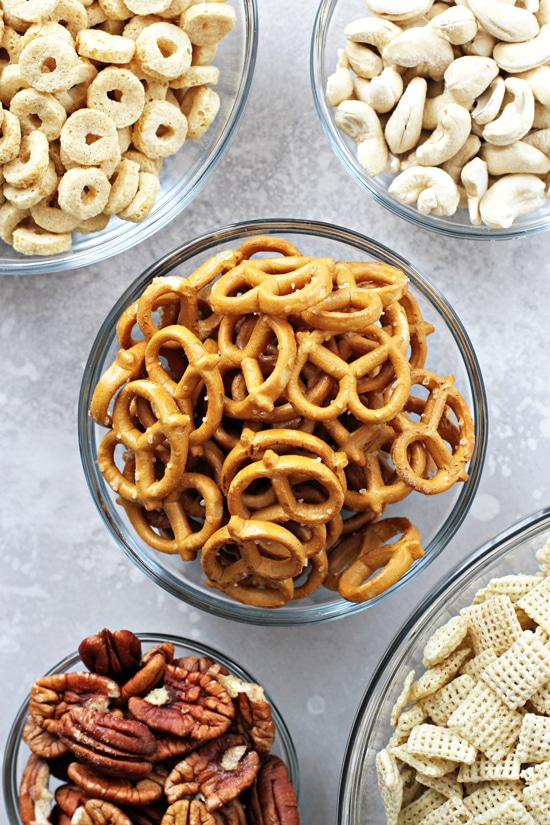 Cereal, nuts and pretzels in glass bowls.