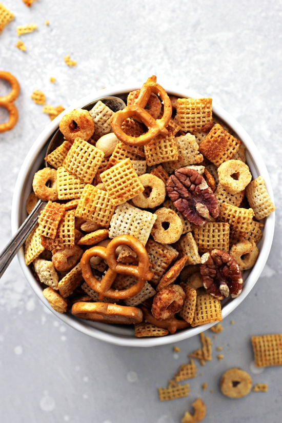 A bowl of Gluten Free Chex Mix with a spoon in the dish.