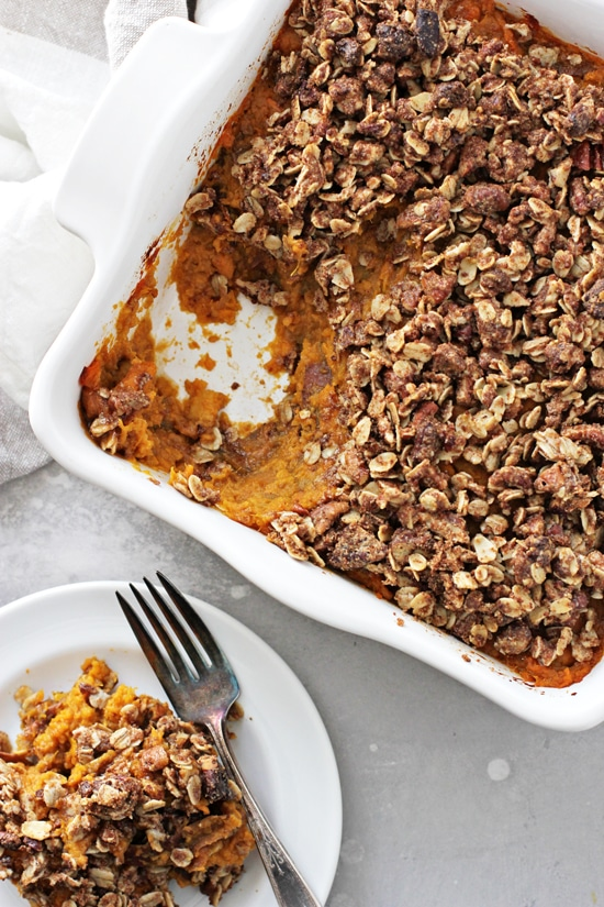 A scoop of Vegan Sweet Potato Casserole on a dish with more to the side.