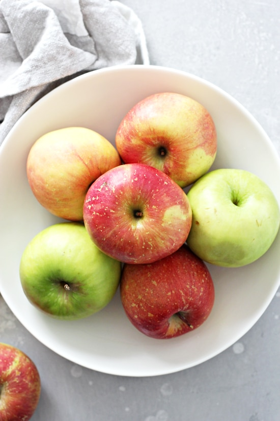A white bowl filled with red and green apples.