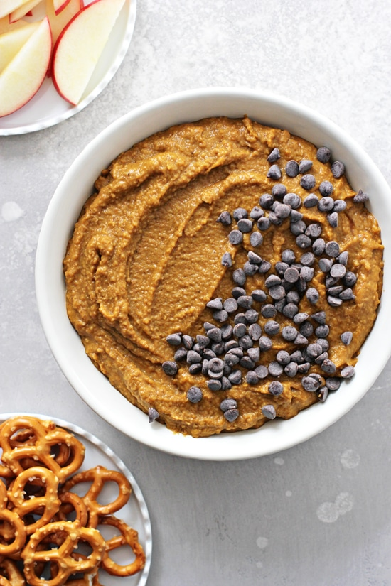 Pumpkin Spice Hummus in a bowl with pretzels and apples to the side.