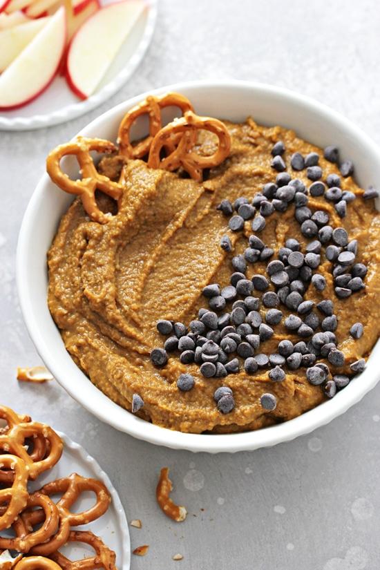 Sweet Pumpkin Hummus in a bowl with a few pretzels.