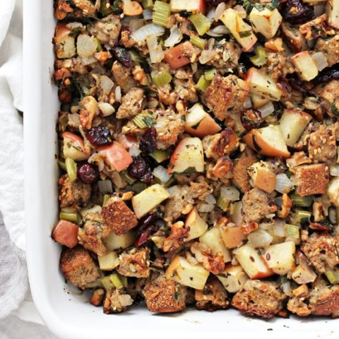 A white baking dish filled with Dairy Free Apple Walnut Stuffing.
