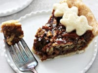 A slice of Dairy Free Pecan Pie with a bite taken out with a fork.
