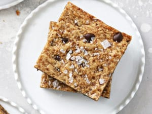 Two Dairy Free Blondies stacked on a white plate.