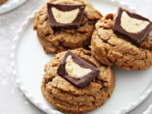Three Gluten Free Peanut Butter Cup Cookies on a white plate.