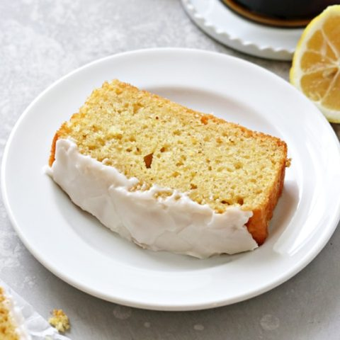 A slice of Dairy Free Lemon Drizzle Cake with coffee to the side.