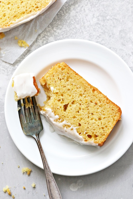 A slice of Dairy Free Lemon Drizzle Loaf with a bite taken out with a fork.