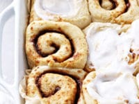 A baking dish filled with partially iced Dairy Free Cinnamon Rolls.