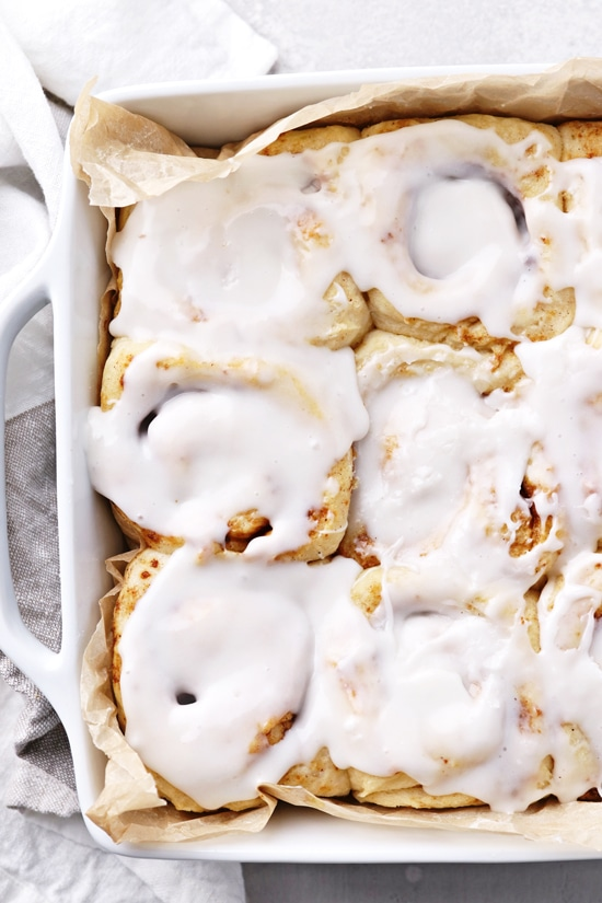 A white baking dish filled with iced Dairy Free Cinnamon Buns.