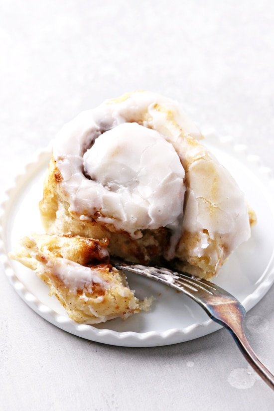 A Non Dairy Cinnamon Bun on a plate with a fork.