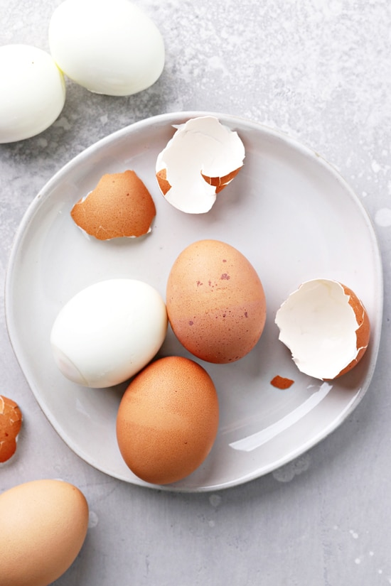 Partially peeled hard boiled eggs on a plate.