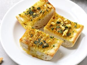Three slices of Dairy Free Garlic Bread on a white plate.