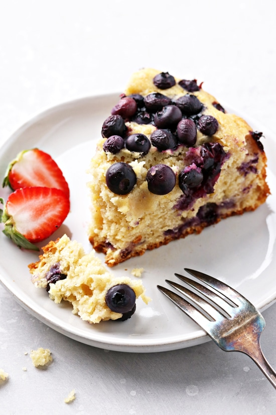 A slice of Dairy Free Blueberry Coffee Cake with a bite taken out.
