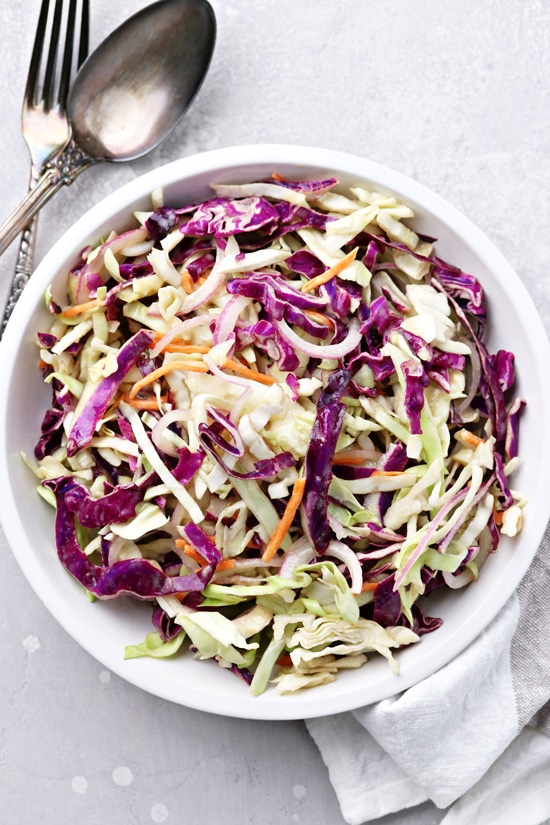 Mayo Free Coleslaw in a bowl with utensils to the side.