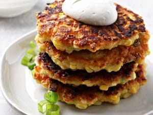 Four Dairy Free Corn Fritters stacked on a plate.