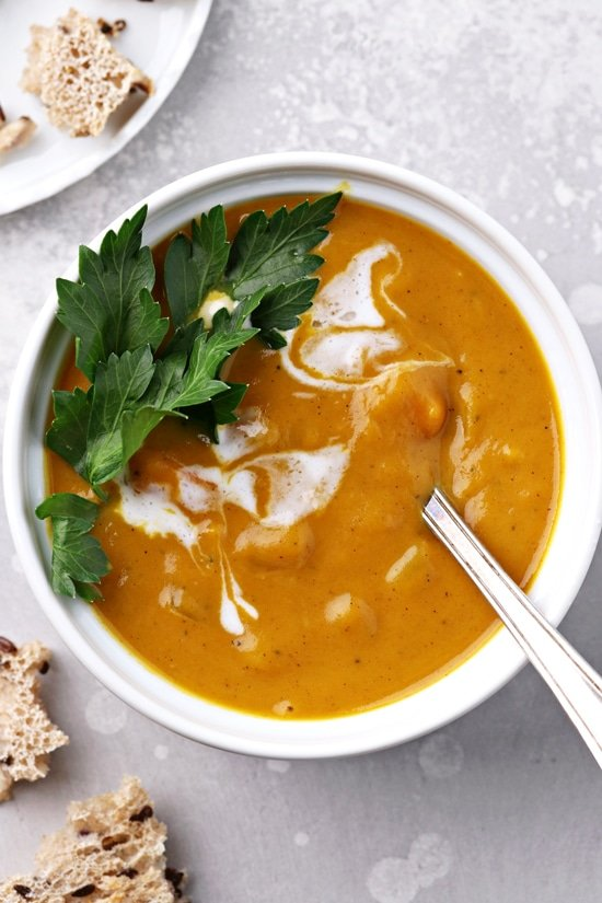 A white bowl of Pumpkin Soup with Coconut Milk.