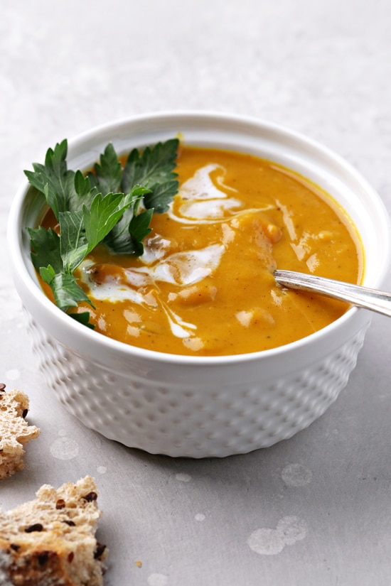 A bowl of Non Dairy Pumpkin Soup with torn bread to the side.
